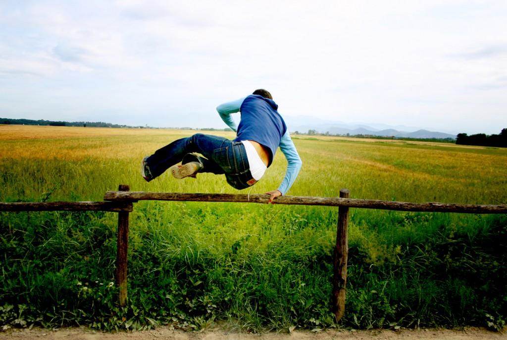 Man springt over een hek