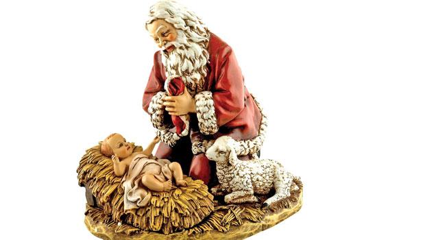 kerstman knielt bij kribbe met kindje jezus kerst