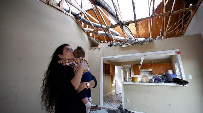 Lindsay Diaz staat met haar 7 maanden oude zoontje in de woonkamer van het huis dat gerepareerd had moeten worden. Dit is voor het per ongeluk werd gesloopt.