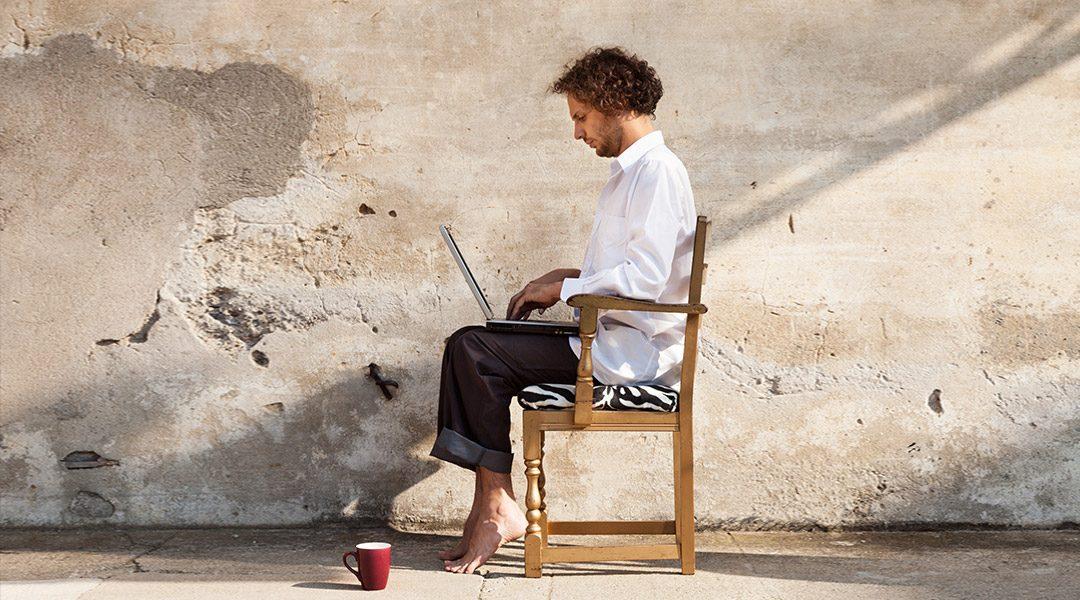 man zit met laptop op een stoel