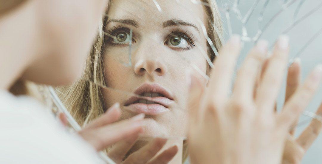 vrouw kijkt in gebroken spiegel