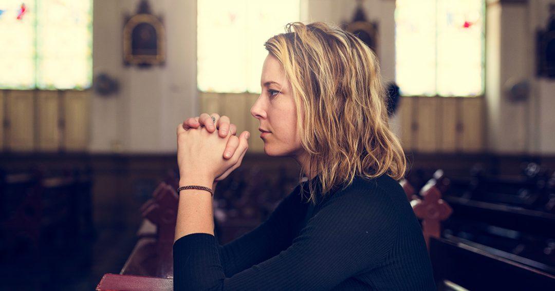 vrouw bidt in de kerk